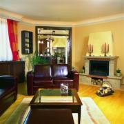 A barna ülőgarnitúra és a négyzet alakú asztal et a nappalit föld eleművé teszi.